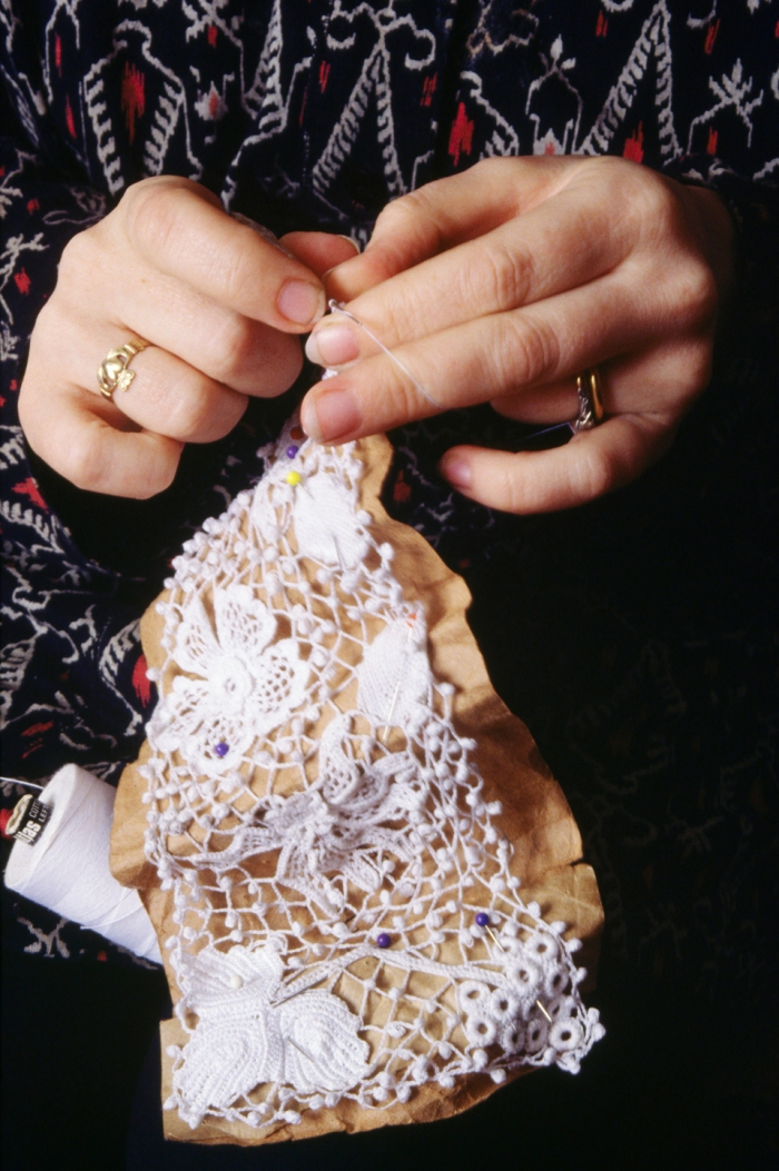 ca. 1980-1996, Ireland --- Marie Connelly makes clones knots between the main motifs in a piece of hand-crocheted lace. --- Image by © Jacqui Hurst/CORBIS
